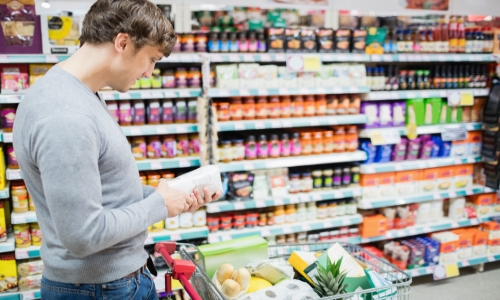 Man checking the ingredients on a jar in a grocery
